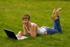 Mulher nova feliz com caderno e o telefone móvel Imagem de Stock Royalty Free