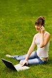 Mulher nova feliz com caderno e o telefone móvel Imagens de Stock