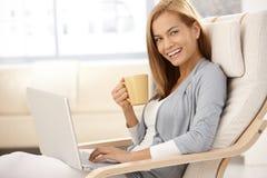 Mulher nova feliz com a caneca do computador e de café Imagens de Stock Royalty Free