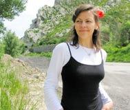 Mulher nova feliz com flor vermelha Foto de Stock