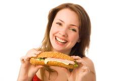 Mulher nova feliz com um hot-dog Imagens de Stock