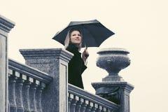 Mulher nova feliz da forma com guarda-chuva que anda na rua da cidade Fotografia de Stock