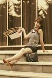Mulher nova feliz da forma com os sacos de compras que sentam-se nas etapas da alameda foto de stock royalty free
