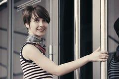 Mulher nova feliz da forma em camiseta de alças listrada ao lado da porta da alameda Fotos de Stock Royalty Free