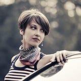 Mulher nova feliz da forma em camiseta de alças listrada que inclina-se em seu carro Fotografia de Stock