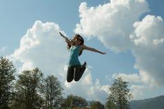 Mulher nova feliz dark-haired bonita que salta altamente no ar, de encontro ao fundo do céu azul do verão Imagem horizontal imagem de stock royalty free