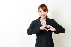 A mulher nova feliz do buisiness fá-lo a forma do coração perto Fotografia de Stock Royalty Free