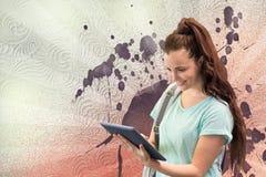 Mulher nova feliz do estudante que mantém uma tabuleta contra o fundo chapinhado do branco, o vermelho e o roxo Fotografia de Stock Royalty Free