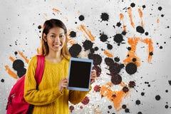 Mulher nova feliz do estudante que mantém uma tabuleta contra o fundo chapinhado cinzento, amarelo e preto Imagens de Stock Royalty Free