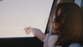 Mulher nova feliz do turista com cabelo do voo e para distribuir da janela no carro que move-se ao longo do deserto quente ensola vídeos de arquivo