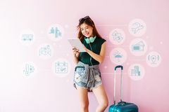 Mulher nova feliz do viajante com mala de viagem usando a tabuleta para a viagem M Fotos de Stock Royalty Free