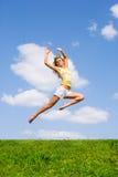 A mulher nova feliz está dançando em um campo Imagem de Stock Royalty Free