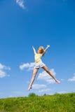 A mulher nova feliz está saltando em um campo Foto de Stock