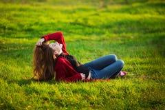 Mulher nova feliz Fêmea bonita com cabelo saudável longo que aprecia a luz do sol no parque que senta-se na grama verde Mola Fotos de Stock Royalty Free