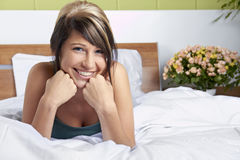 Mulher nova feliz na cama imagem de stock
