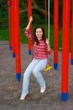 Mulher nova feliz no campo de jogos Foto de Stock