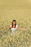 A mulher nova feliz no campo de milho aprecia o por do sol Fotos de Stock