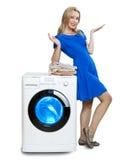 A mulher nova feliz perto da máquina de lavar nova fotos de stock