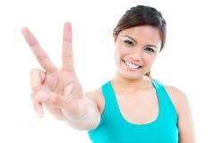 Mulher nova feliz que mostra o sinal de paz imagens de stock royalty free