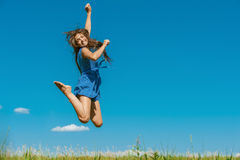 Mulher nova feliz que salta altamente fotografia de stock royalty free
