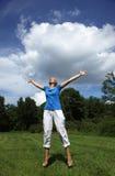Mulher nova feliz que salta em um campo Foto de Stock Royalty Free