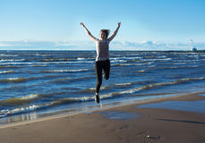 Mulher nova feliz que salta na praia fotografia de stock royalty free