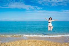 Mulher nova feliz que salta na praia imagem de stock