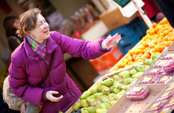 Mulher nova feliz que seleciona frutas Imagens de Stock