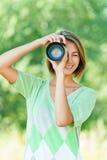 A mulher nova fotografou a câmera de SLR Fotografia de Stock Royalty Free