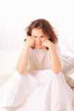 Mulher nova irritada que senta-se na cama Imagem de Stock
