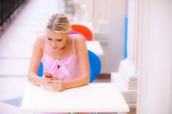 A mulher nova lê sms no café Imagens de Stock Royalty Free
