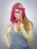 A mulher nova mostra um cabelo louro através de um frame fotografia de stock