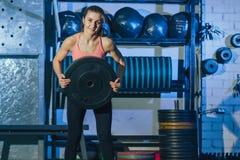 Mulher nova muscular da aptidão que levanta um crossfit do peso no gym Barbell do deadlift da mulher da aptidão Mulher de Crossfi Imagem de Stock