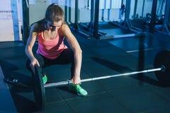 Mulher nova muscular da aptidão que levanta um crossfit do peso no gym Barbell do deadlift da mulher da aptidão Mulher de Crossfi Fotografia de Stock Royalty Free