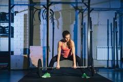 Mulher nova muscular da aptidão que levanta um crossfit do peso no gym Barbell do deadlift da mulher da aptidão O gym no vermelho Imagens de Stock Royalty Free