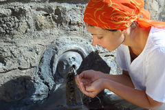 Mulher nova na água bebendo do kerchief Fotos de Stock Royalty Free