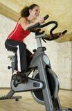 Mulher nova na bicicleta de exercício Fotografia de Stock Royalty Free