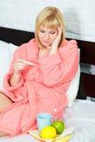 Mulher nova na cama que está com a gripe fotos de stock