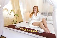 A mulher nova na casa veste-se na cama Fotos de Stock