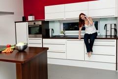 Mulher nova na cozinha imagens de stock royalty free