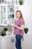 Mulher nova na cozinha fotografia de stock