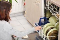 Mulher nova na cozinha que faz o housework. fotos de stock