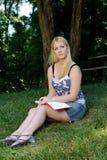 Mulher nova na escrita do parque no jornal ou no diário Fotografia de Stock