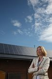 Mulher nova na frente da casa solar-psta imagem de stock royalty free