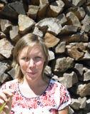Mulher nova na frente da pilha de madeira Fotos de Stock Royalty Free