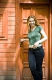 Mulher nova na frente de sua casa nova das férias Foto de Stock