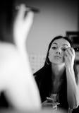 Mulher nova na frente do espelho no quarto da composição Fotografia de Stock Royalty Free