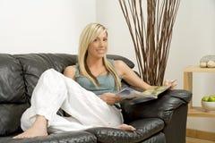Mulher nova na leitura do sofá Fotografia de Stock