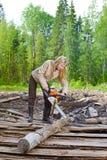 A mulher nova na madeira vê uma árvore uma serra de cadeia Imagens de Stock