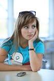 Mulher nova na tabela no witn do café um telefone Foto de Stock Royalty Free